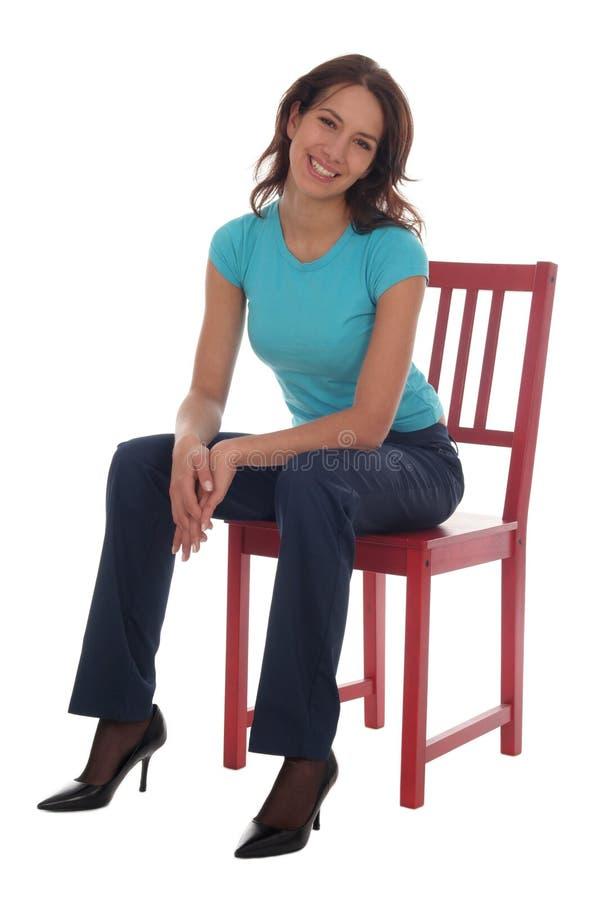 De zitting van de vrouw op stoel stock afbeelding
