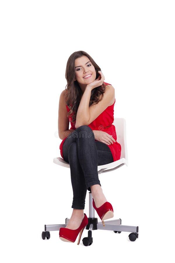 De zitting van de vrouw op stoel stock fotografie