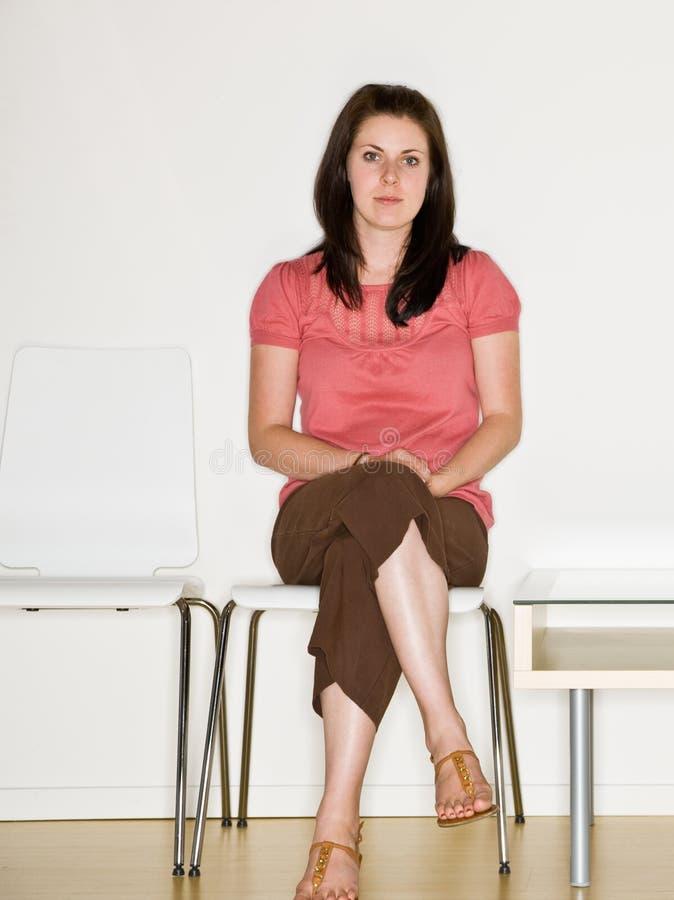De zitting van de vrouw in wachtkamer stock afbeeldingen