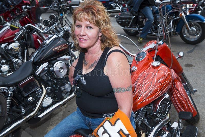 De zitting van de vrouwenruiter op haar fiets in de stad van Sturgis, in Zuid-Dakota, de V.S., tijdens de jaarlijkse Sturgis-Moto stock fotografie