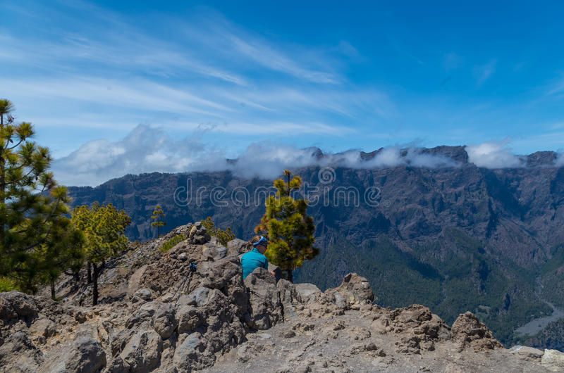 De zitting van de vrouwenwandelaar op de top met panorama, La Palma stock fotografie