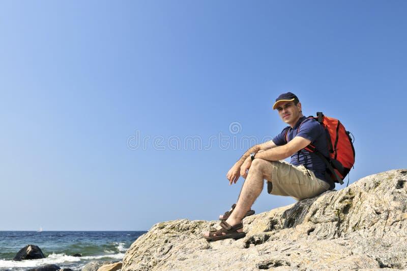 De zitting van de wandelaar op een rots royalty-vrije stock foto