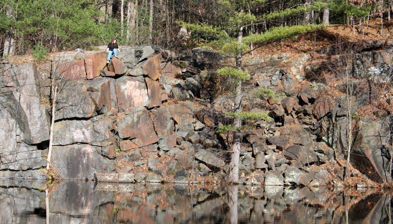 De zitting van de wandelaar op rotsachtige richel door nog water royalty-vrije stock foto