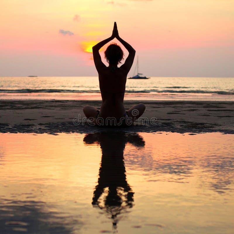 De zitting van de yogavrouw in lotusbloem stelt op het strand stock afbeeldingen