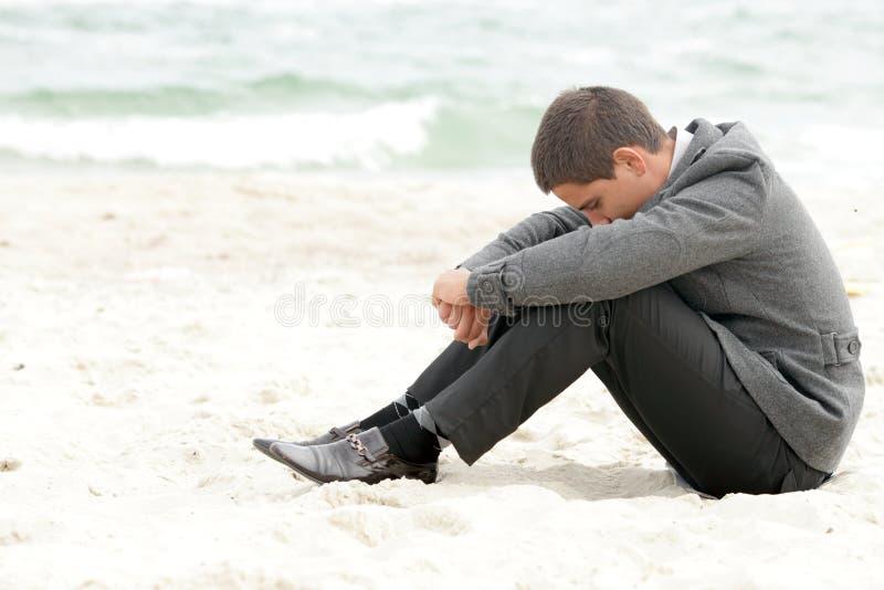 De zitting van de zakenman op het alleen strand stock foto