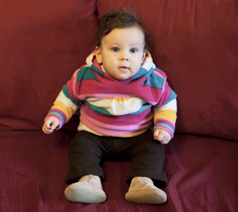 De zitting van het babymeisje stock foto's