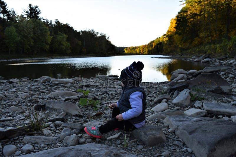 De zitting van het babymeisje bij rivier stock afbeeldingen