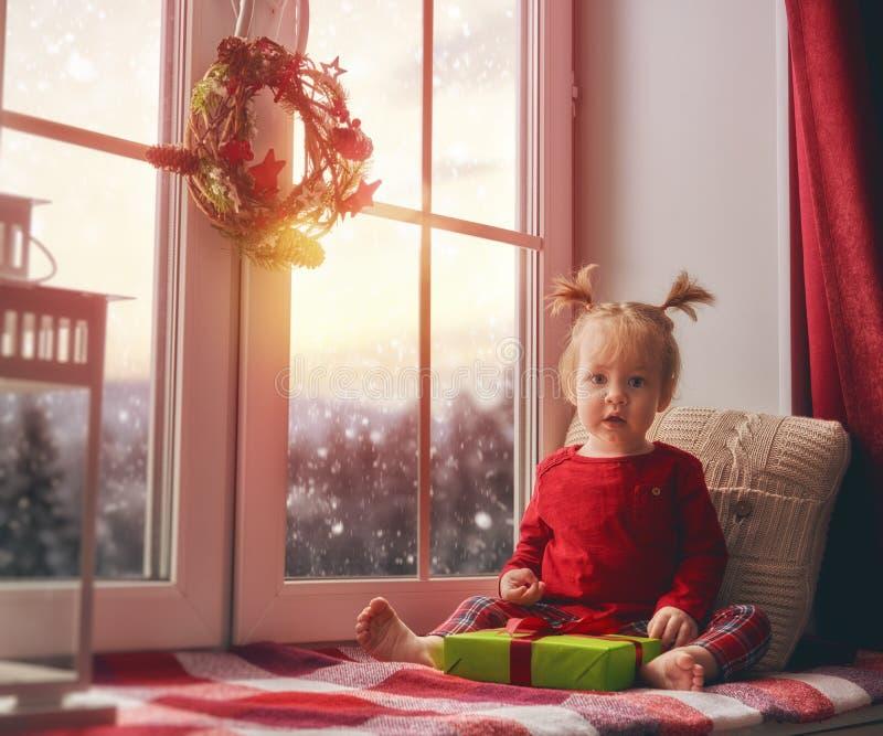De zitting van het babymeisje door het venster stock fotografie