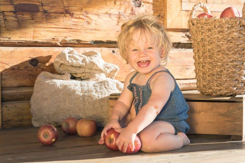 De zitting van het babymeisje en het Glimlachen dichtbij Houten Schuur stock afbeeldingen