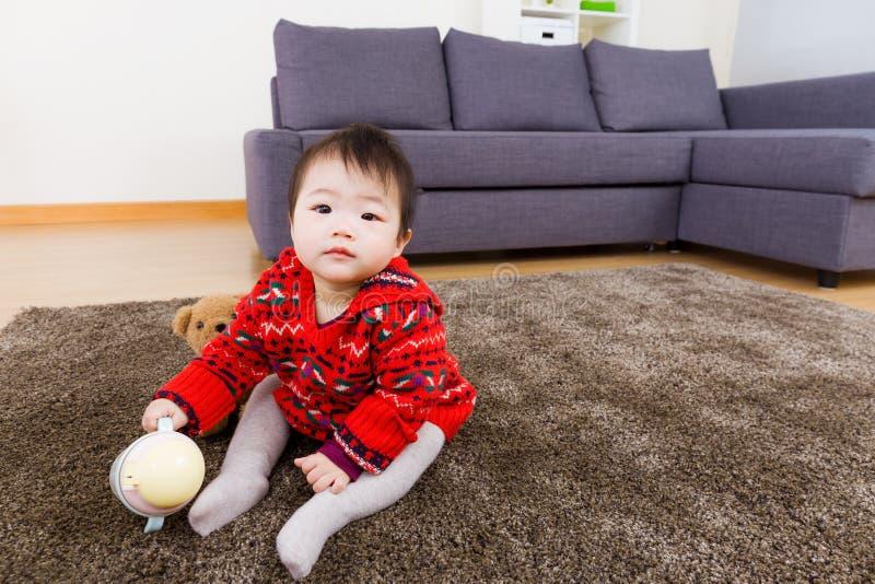 De zitting van het babymeisje op tapijt met waterbodem en pop stock fotografie