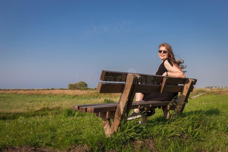 De zitting van het blondemeisje op een bank royalty-vrije stock foto's