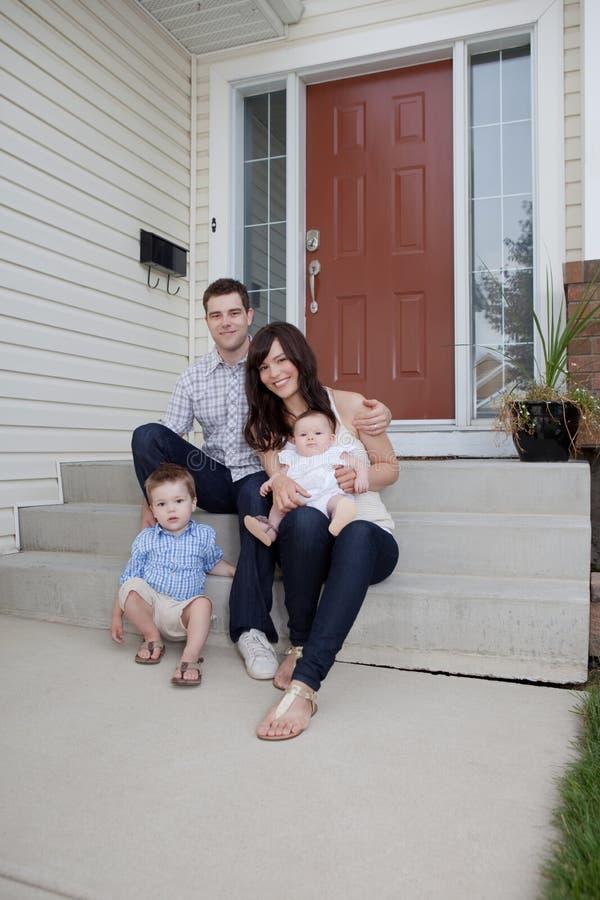 De Zitting van het familieportret in Front Of Their House stock foto