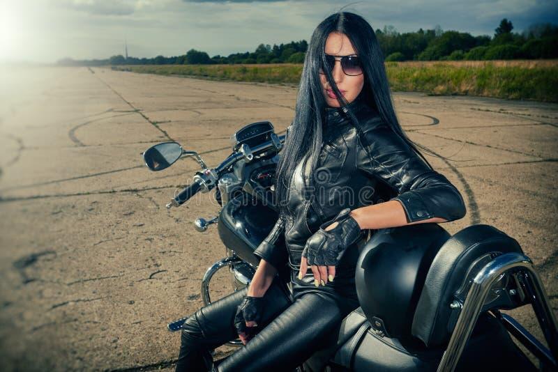 De zitting van het fietsermeisje op een motorfiets royalty-vrije stock afbeeldingen