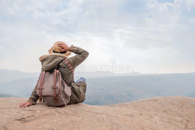 De zitting van het Hipstermeisje in rotsachtig van berg stock foto