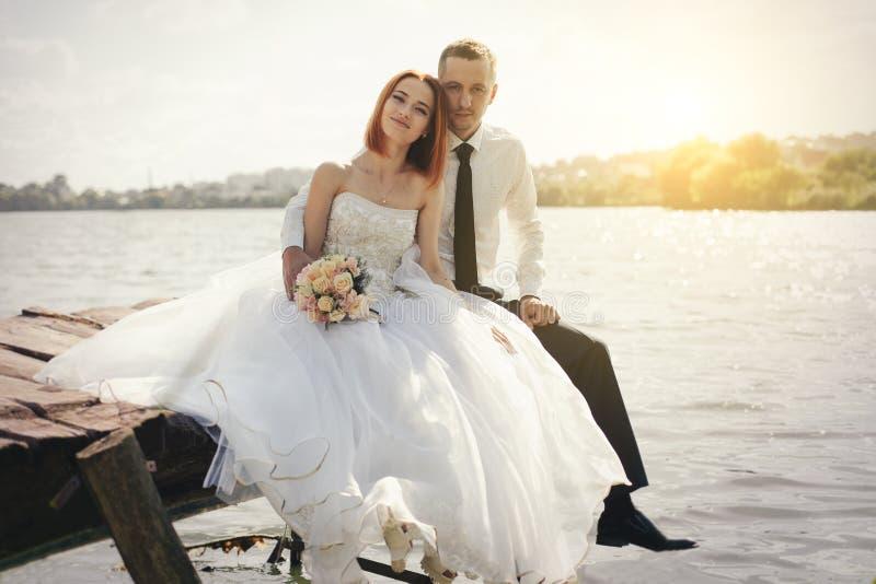 De zitting van het huwelijkspaar op brug dichtbij meer op zonsondergang bij huwelijksdag Bruid en Bruidegom in Liefde royalty-vrije stock afbeeldingen