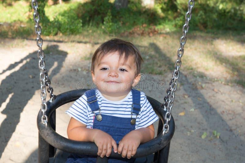 De zitting van het jongenskind op schommeling in tuinspeelplaats stock foto's