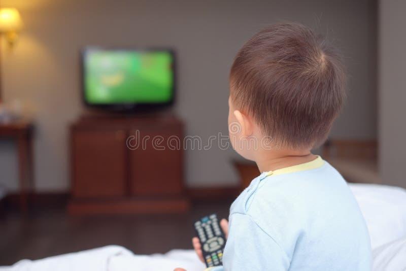 de zitting van het de jongenskind van de peuterbaby in bed die de TV-afstandsbediening houden en op televisie letten stock foto's