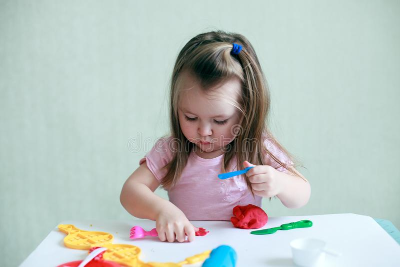 De zitting van het kindmeisje bij lijst het spelen met kleurrijke klei binnen, concept peuteronderwijs en kunsttherapie stock afbeelding
