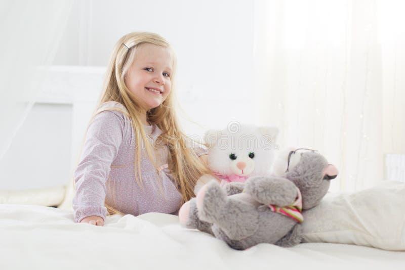 De zitting van het kindmeisje in het bed met haar zacht speelgoed stock foto