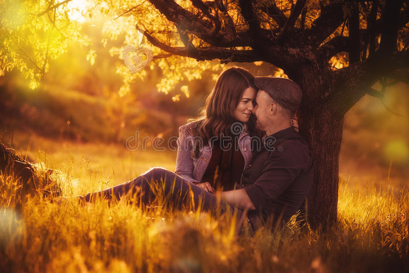 De zitting van het liefdepaar onder een boom in de kleurrijke de lentetuin stock afbeeldingen