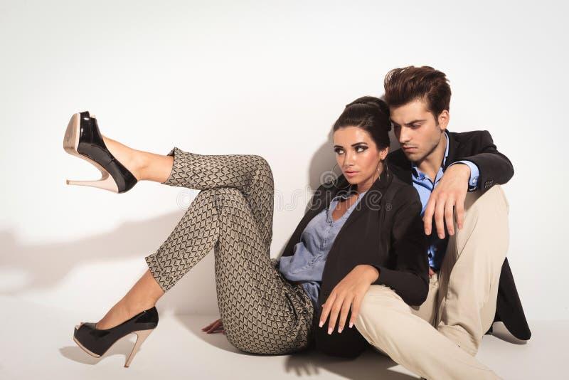 De zitting van het manierpaar op de vloer samen stock foto