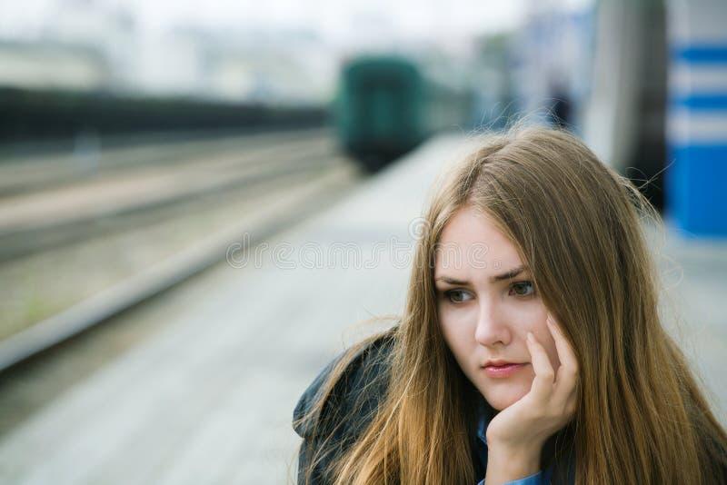 De zitting van het meisje bij het station stock foto's