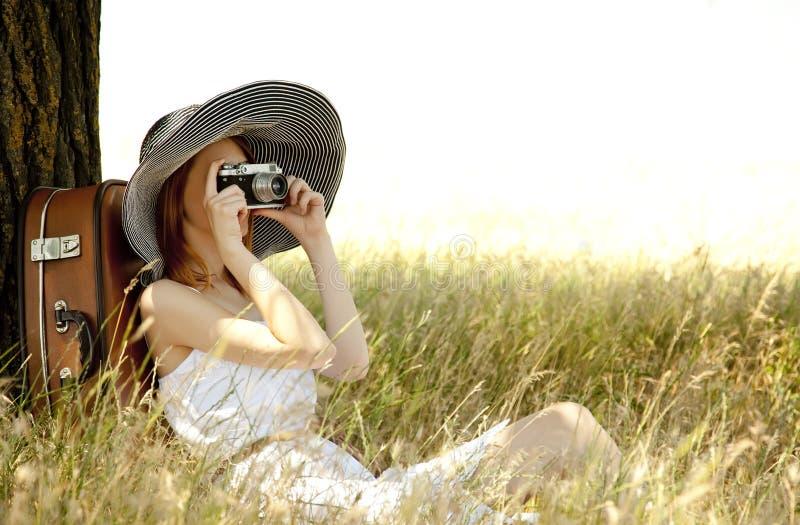 De zitting van het meisje dichtbij boom met uitstekende camera. royalty-vrije stock afbeeldingen