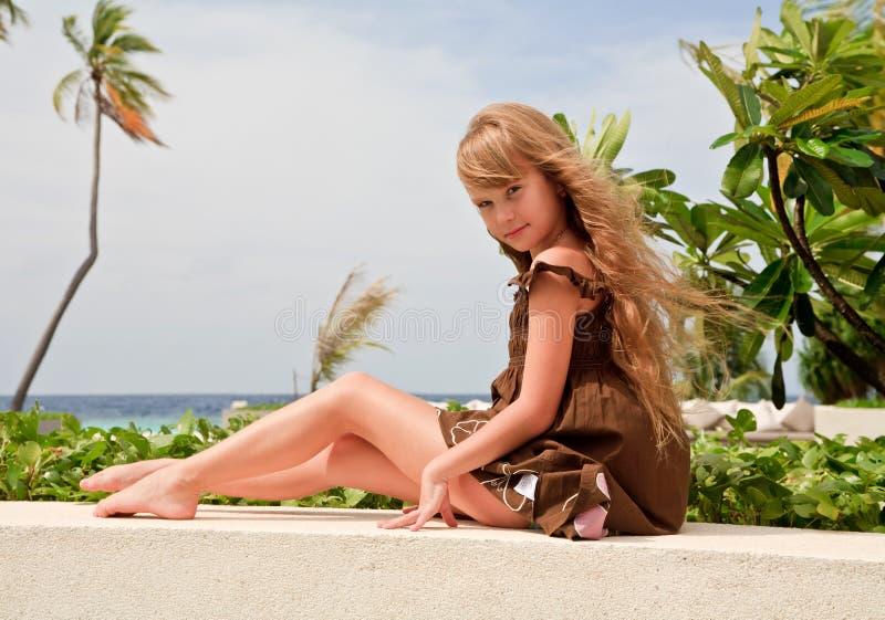 De zitting van het meisje dichtbij oceaan royalty-vrije stock foto