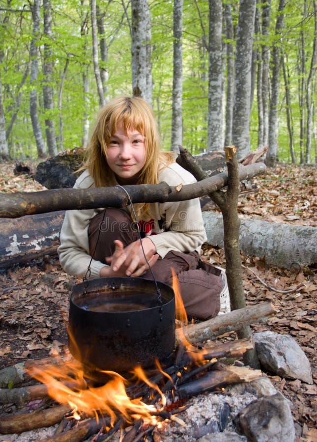 De zitting van het meisje dichtbij van vuur in bos royalty-vrije stock afbeelding