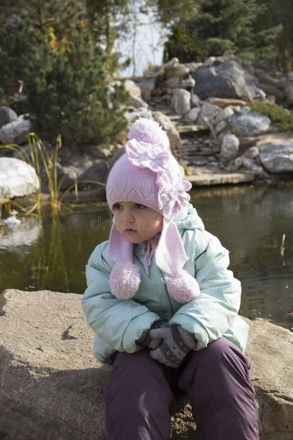 De zitting van het meisje dichtbij vijver royalty-vrije stock fotografie