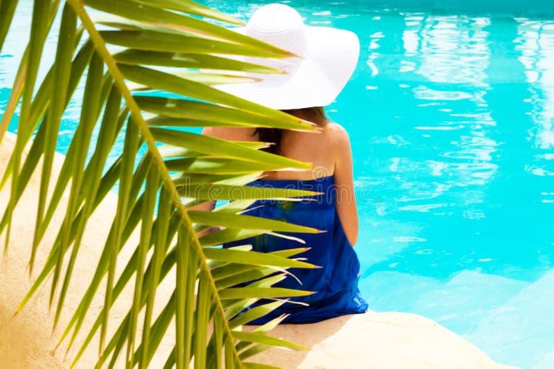 De zitting van het meisje door de pool royalty-vrije stock fotografie