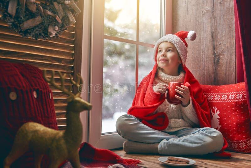 De zitting van het meisje door het venster royalty-vrije stock afbeelding