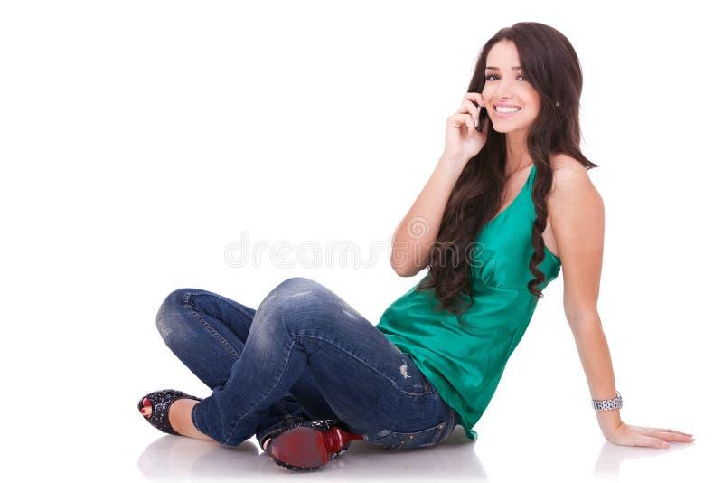 De zitting van het meisje en het spreken op telefoon stock afbeeldingen