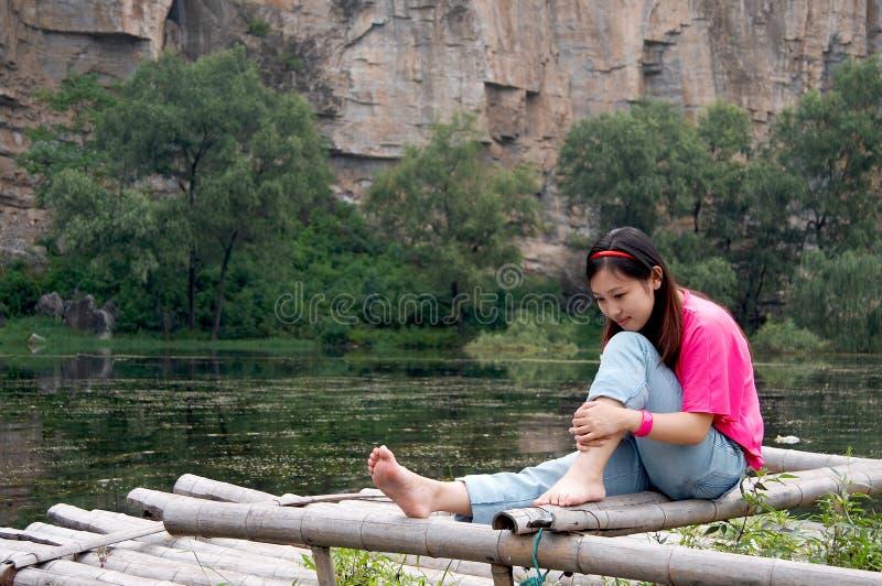 De zitting van het meisje op bamboevlot royalty-vrije stock foto