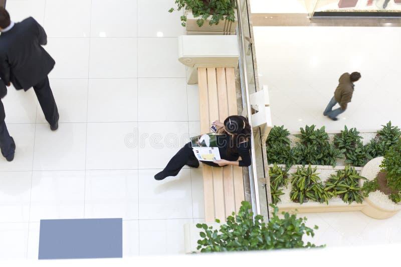 De zitting van het meisje op bank en lezing een tijdschrift royalty-vrije stock afbeelding