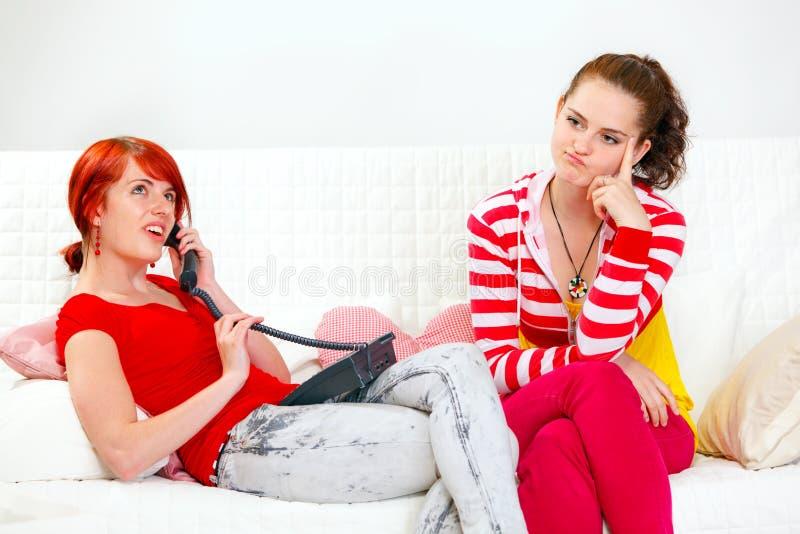 De zitting van het meisje op bank terwijl haar meisjetelefoon stock afbeeldingen