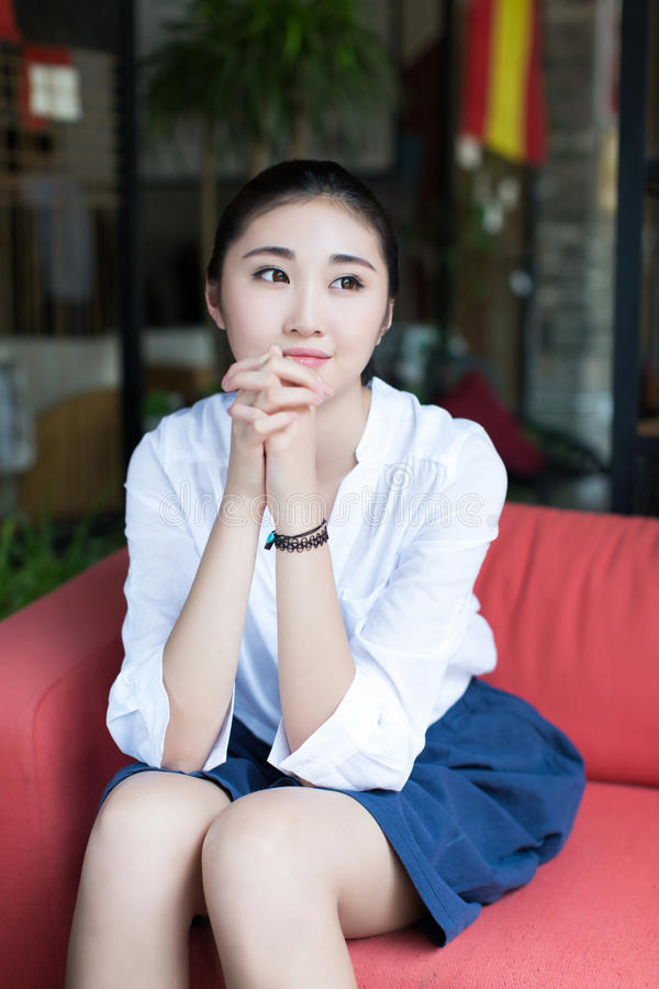 De zitting van het meisje op de bank royalty-vrije stock fotografie