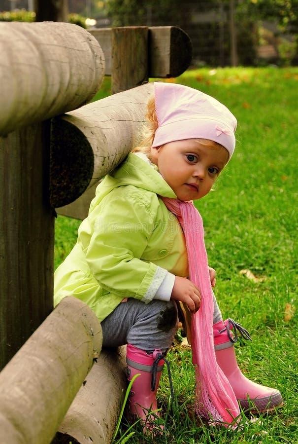 De zitting van het meisje op de houten omheining in een park. stock afbeeldingen
