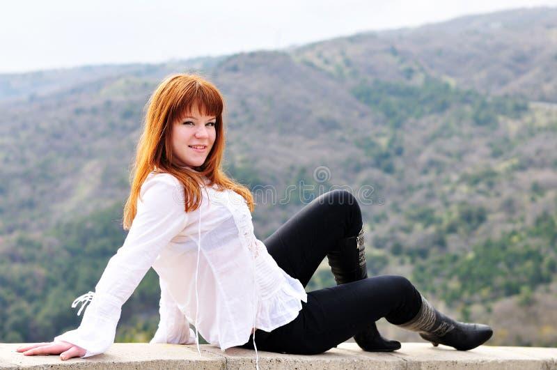 De zitting van het meisje op de muur royalty-vrije stock foto