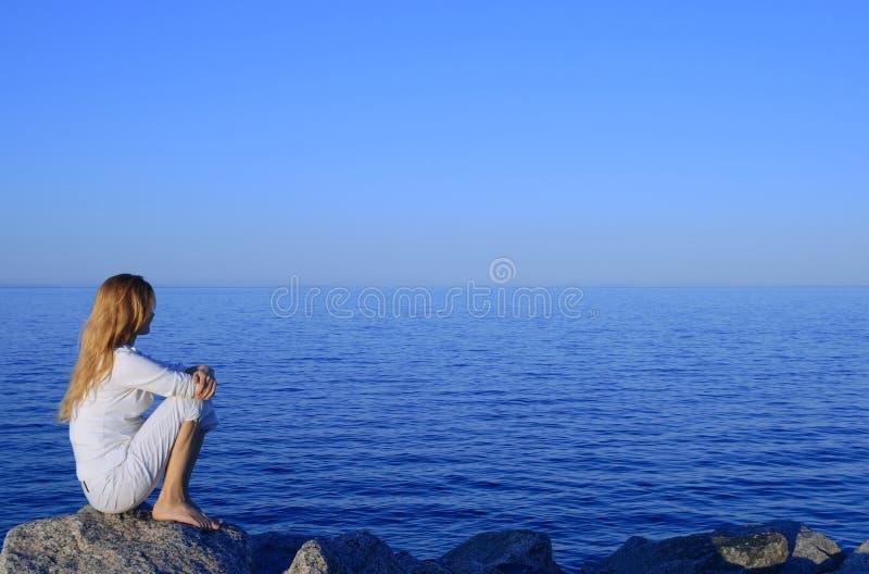 De zitting van het meisje op de rots door het vreedzame overzees stock afbeeldingen