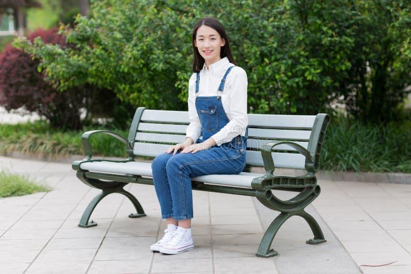 De zitting van het meisje op een bank stock foto