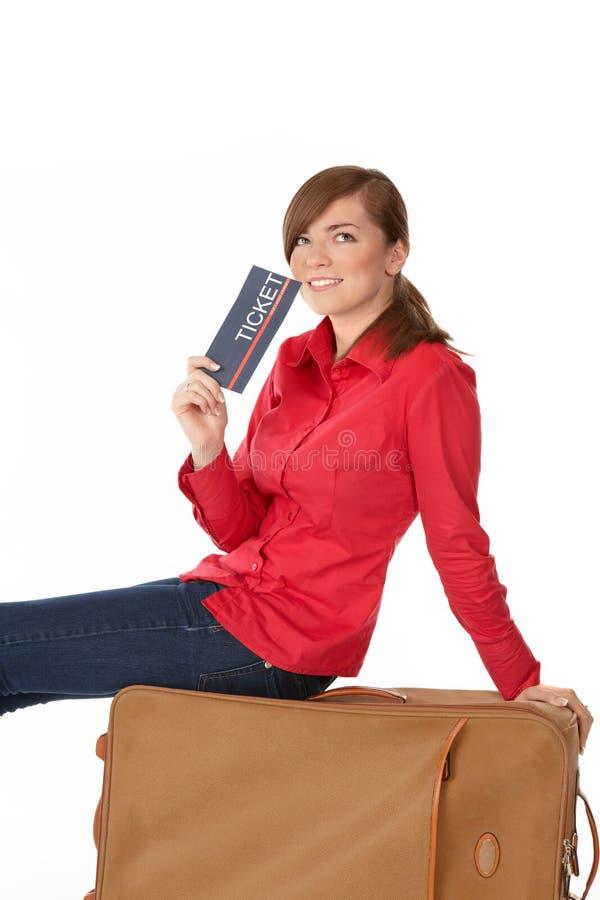De zitting van het meisje op een koffer stock foto's