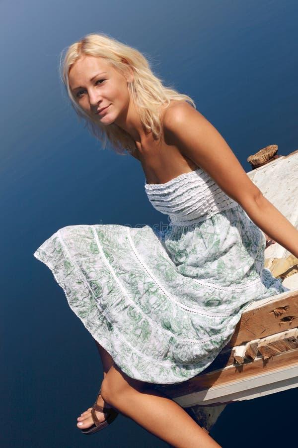 De zitting van het meisje op een pijler bij de rivierbank royalty-vrije stock fotografie