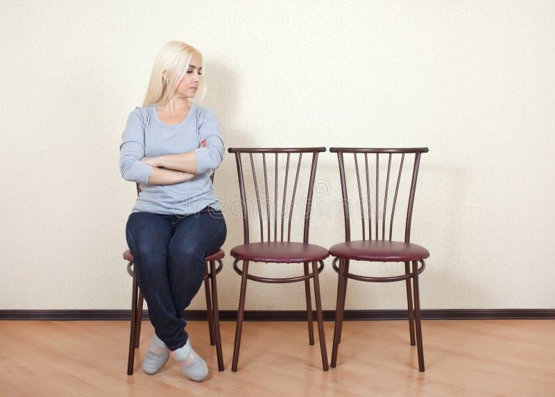 De zitting van het meisje op een stoel stock foto's