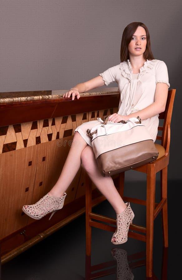 De zitting van het meisje op een stoel in een staaf stock afbeelding