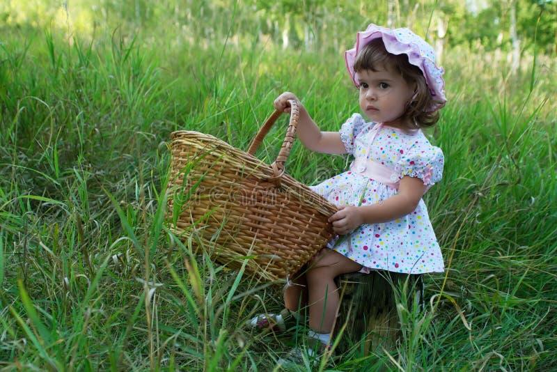 De zitting van het meisje op een stomp en holding een mand stock afbeeldingen