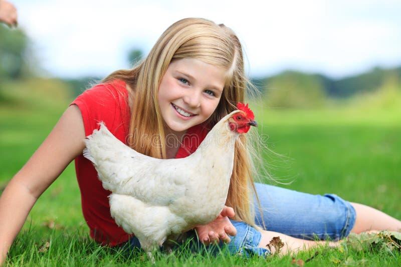 De zitting van het meisje op een weide met haar kip stock foto