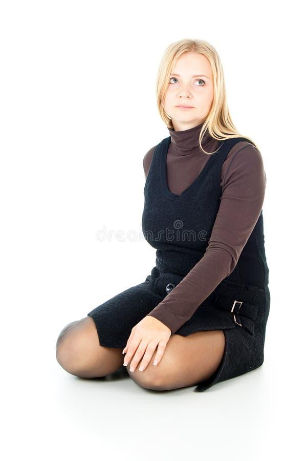De zitting van het meisje op een witte achtergrond stock afbeeldingen