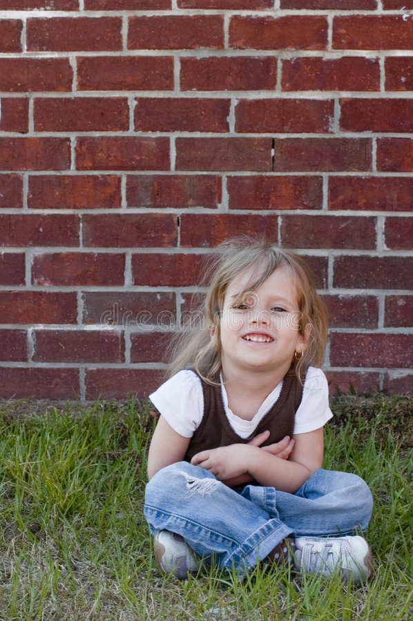De Zitting van het meisje op Gras royalty-vrije stock afbeelding