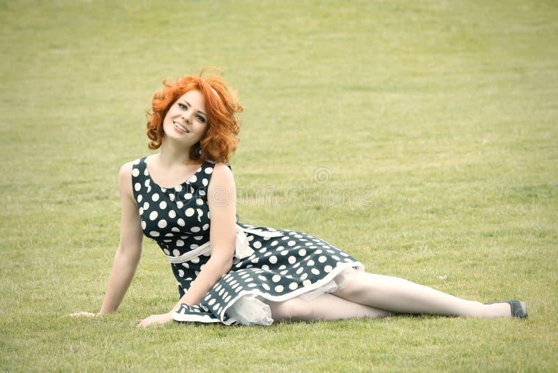 De zitting van het meisje op het gras royalty-vrije stock afbeelding